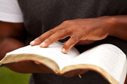 Hand of a man with an open bible
